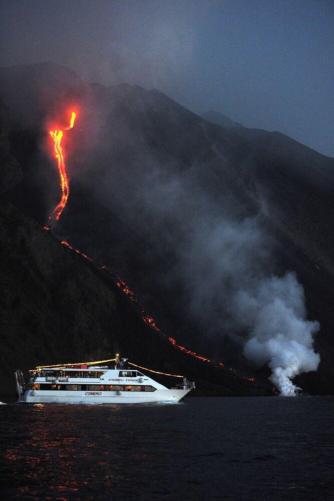 Turisti su una nave vicino al vulcano in eruzione Stromboli, Italia