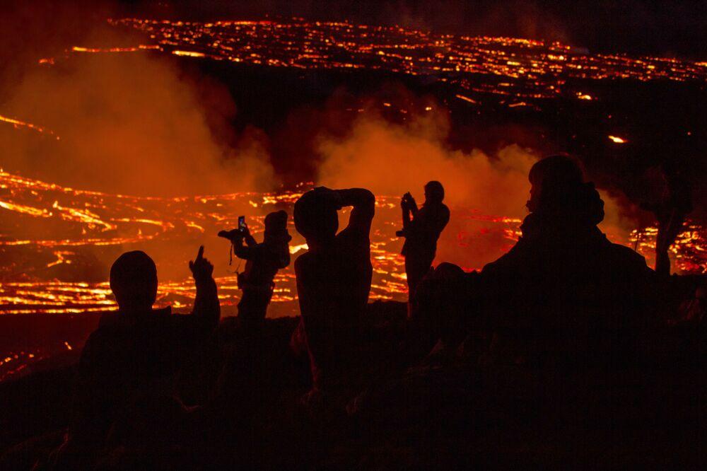 Persone guardano la lava scorrere durante l'eruzione del vulcano nella penisola di Reykjanes, nel sud-ovest dell'Islanda