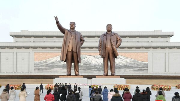 People lay floral tributes in front of the bronze statues of the late leaders Kim Il Sung and his son Kim Jong Il to commemorate the Day of the Shining Star, the birth anniversary of Kim Jong Il, at the Mansudae Grand Monument in Pyongyang, North Korea in this undated photo released by North Korea's Korean Central News Agency (KCNA) on February 17, 2021. - Sputnik Italia