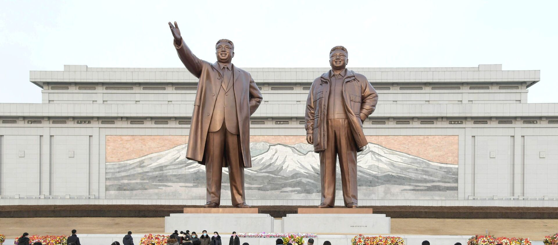 People lay floral tributes in front of the bronze statues of the late leaders Kim Il Sung and his son Kim Jong Il to commemorate the Day of the Shining Star, the birth anniversary of Kim Jong Il, at the Mansudae Grand Monument in Pyongyang, North Korea in this undated photo released by North Korea's Korean Central News Agency (KCNA) on February 17, 2021. - Sputnik Italia, 1920, 28.04.2021