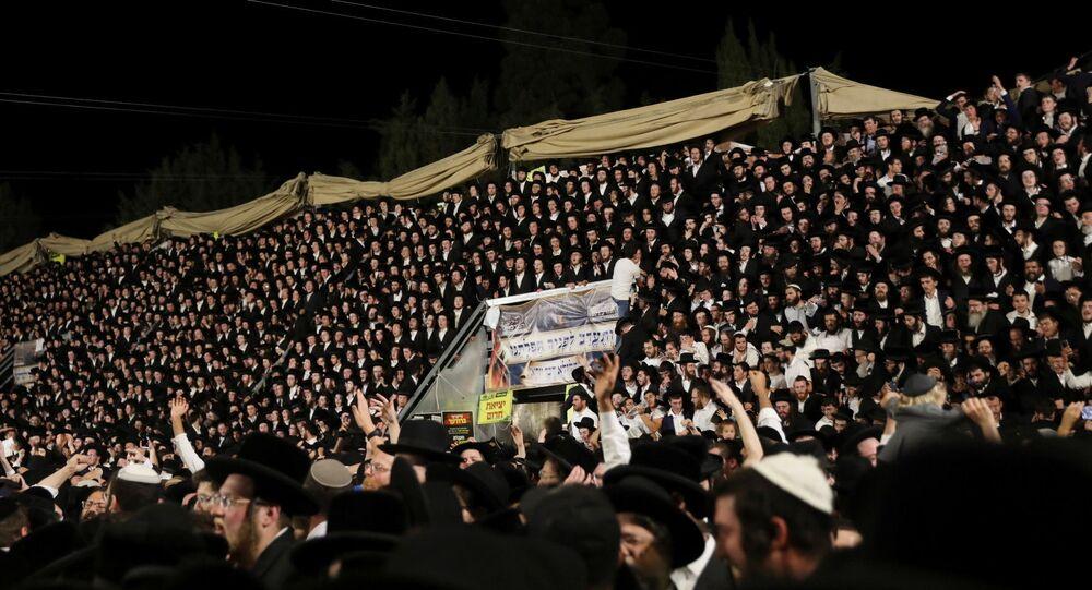 Fedeli ebrei cantano e ballano mentre si trovano sulle tribune all'evento Lag B'Omer sul Monte Meron, nel nord di Israele, il 29 aprile 2021.