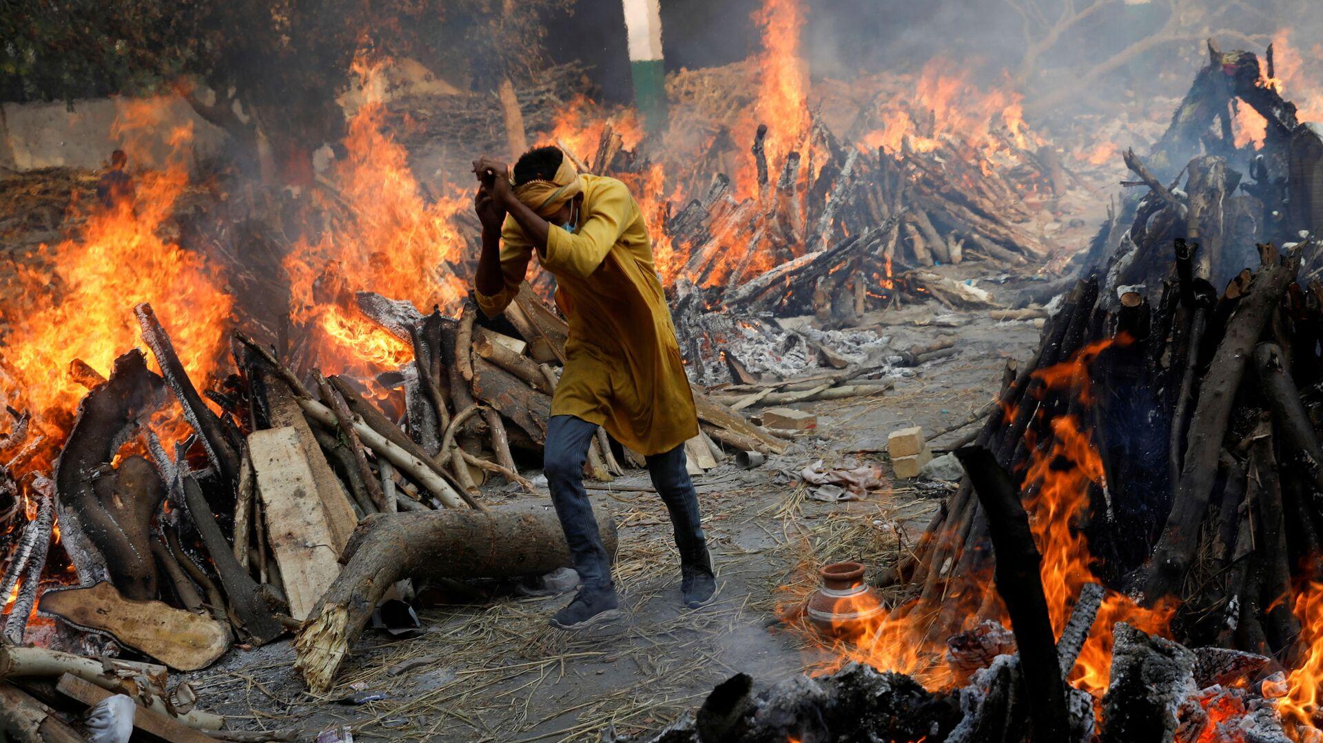 Un uomo passa davanti alle pire funerarie in fiamme dei morti da coronavirus (Covid-19), durante una cremazione di massa, in un crematorio a Nuova Delhi, India 26 aprile 2021.   - Sputnik Italia, 1920, 02.05.2021