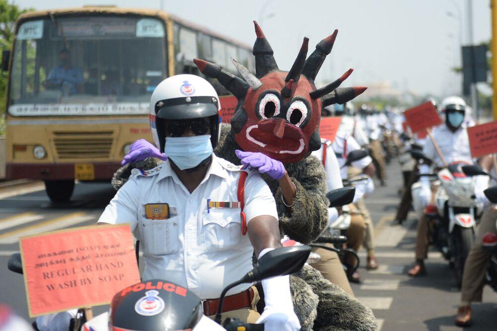 Un agente di polizia vestito da demone simile al coronavirus partecipa con altri agenti di polizia a una manifestazione, Chennai