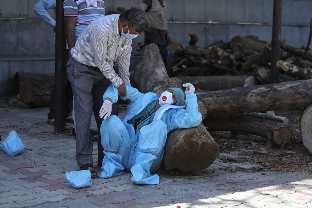 Un parente di un uomo morto a causa del COVID-19 non può sopportare la cremazione a Jammu, in India