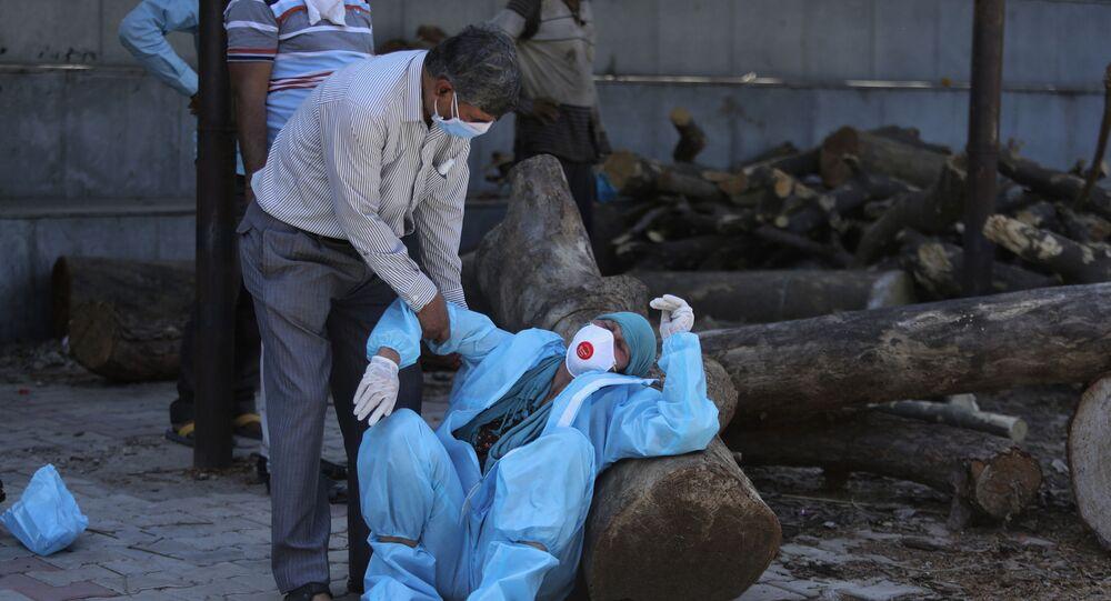 Parente di un uomo morto di COVID-19 collassa durante la cremazione a Jammu, in India