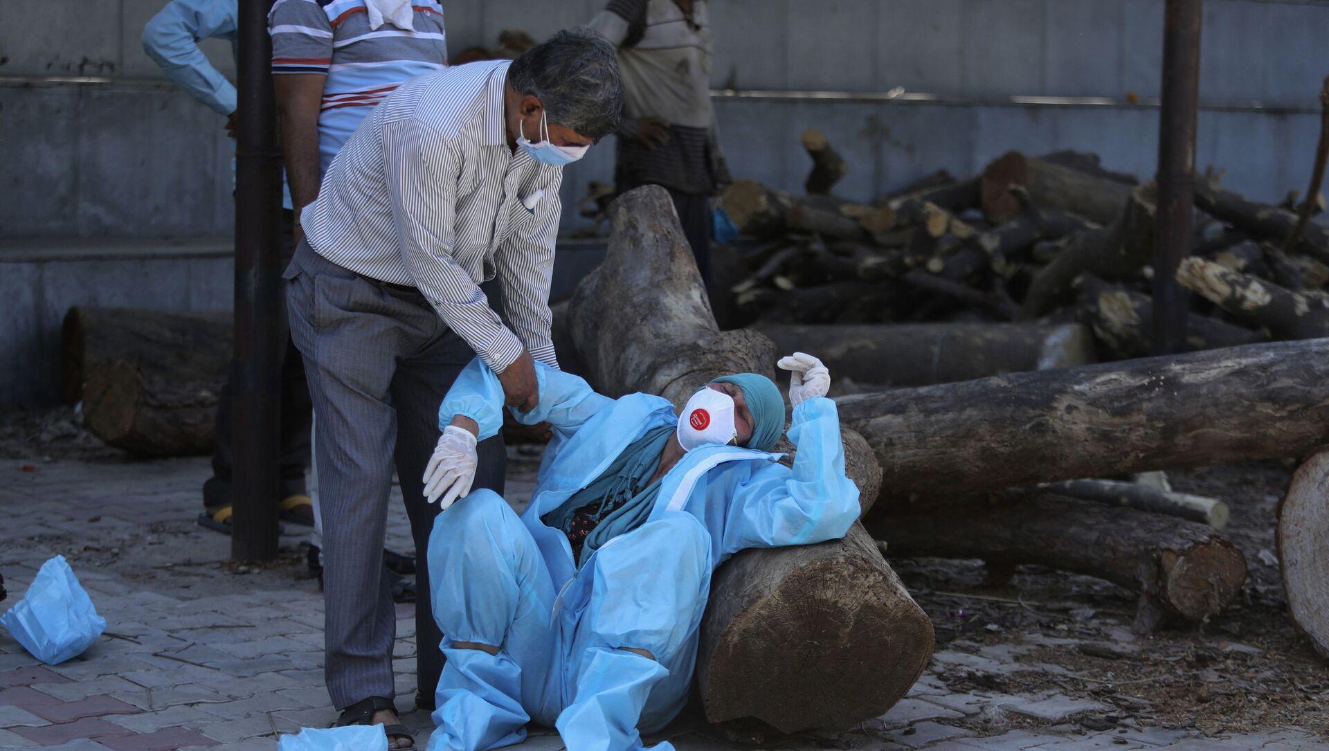 Parente di un uomo morto di COVID-19 collassa durante la cremazione a Jammu, in India - Sputnik Italia, 1920, 07.05.2021