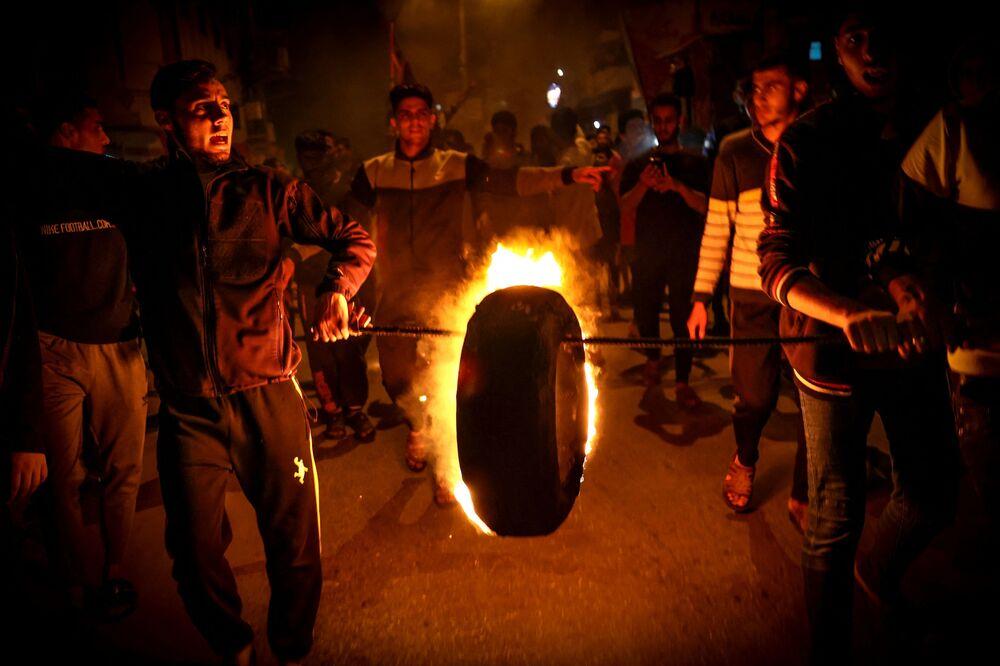 Palestinesi bruciano pneumatici e gridano slogan a sostegno della moschea di Al-Aqsa durante una manifestazione a Gaza City