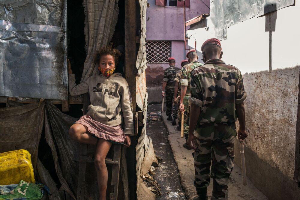 Un bambino in mascherina protettiva in una strada di Antananarivo pattugliata dal personale militare