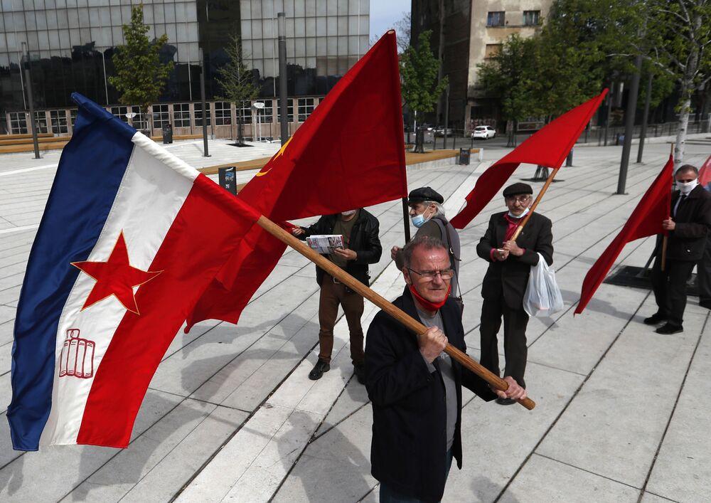 Un uomo sventola una vecchia bandiera jugoslava durante una manifestazione in occasione della Giornata internazionale del Lavoro a Belgrado, in Serbia