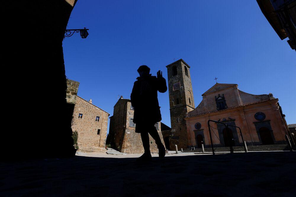 Una residente fa un gesto con la mano mentre attraversa la piazza principale di Civita di Bagnoregio