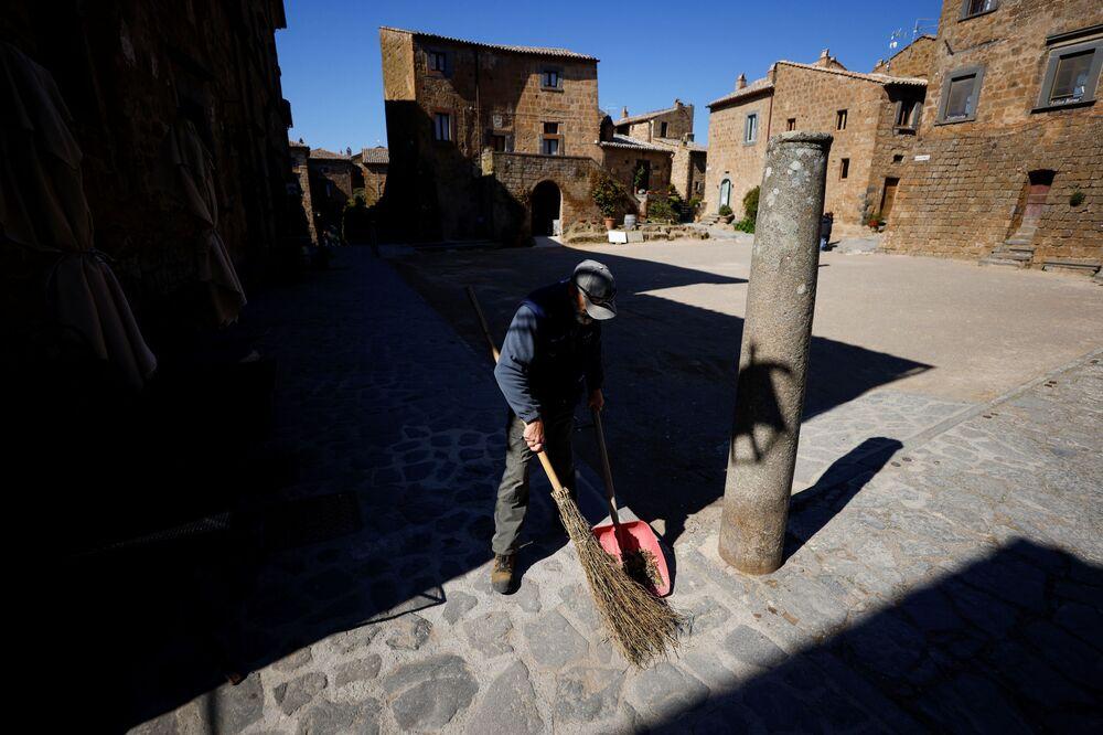 Un addetto alle pulizie pulisce la piazza principale di Civita di Bagnoregio