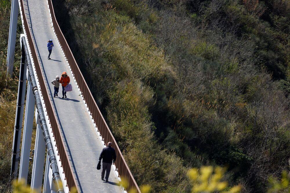 Le persone passeggiano per il ponte che collega Civita di Bagnoregio alla terraferma