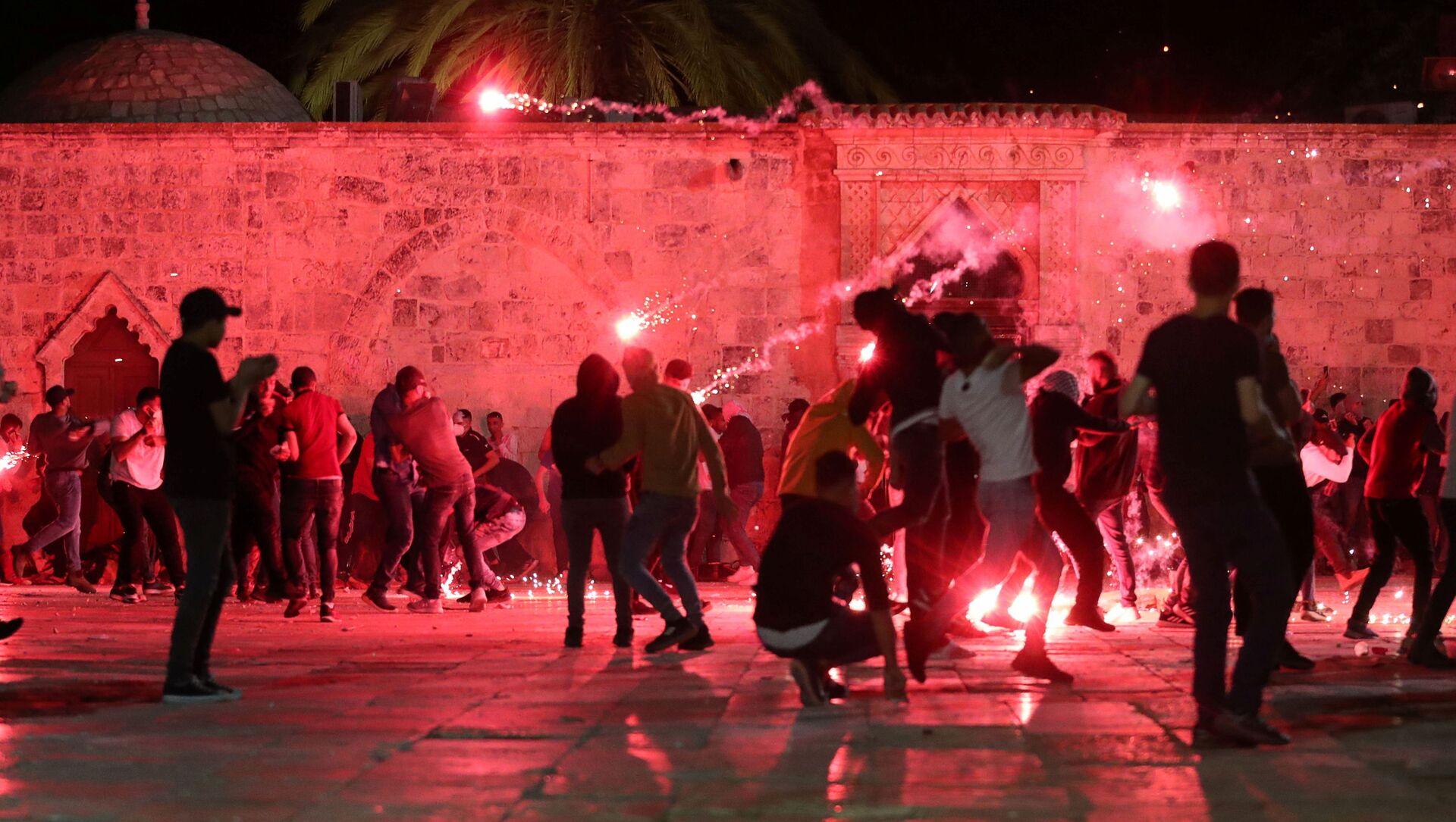Dei palestinesi reagiscono mentre la polizia israeliana spara granate stordenti durante gli scontri nel complesso che ospita la Moschea di Al Aqsa, nota ai musulmani come Santuario Nobile e agli ebrei come Monte del Tempio, tra le tensioni sul possibile sfratto di diverse famiglie palestinesi dalle case sulla dei coloni ebrei nel quartiere di Sheikh Jarrah, nella Città Vecchia di Gerusalemme, 7 maggio 2021 - Sputnik Italia, 1920, 08.05.2021