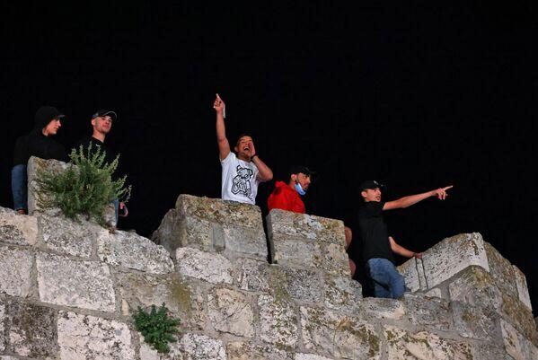 I giovani palestinesi guardano gli scontri  tra gli agenti della polizia israeliana e i manifestanti palestinesi nel complesso che ospita la Moschea di Al Aqsa, nota ai musulmani come Santuario Nobile e agli ebrei come Monte del Tempio, 8 maggio 2021 - Sputnik Italia