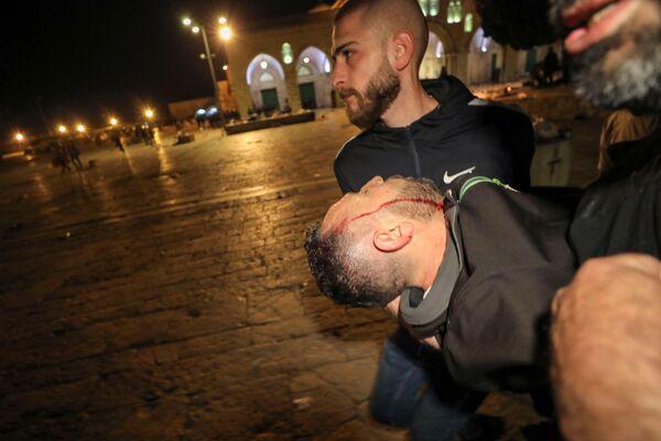 Un palestinese ferito nel corso degli scontri tra gli agenti della polizia israeliana e i manifestanti palestinesi nel complesso che ospita la Moschea di Al Aqsa, nota ai musulmani come Santuario Nobile e agli ebrei come Monte del Tempio, 7 maggio 2021 - Sputnik Italia