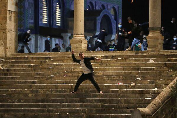 Un palestinese lancia le pietre contro la polizia israeliana durante gli scontri sul Monte del Tempio a Gerusalemme, 7 maggio 2021 - Sputnik Italia