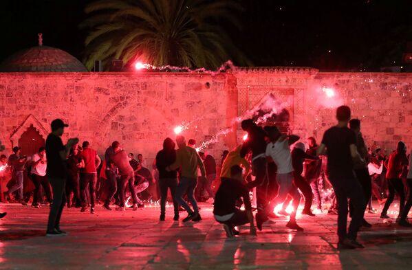 Dei palestinesi reagiscono mentre la polizia israeliana spara granate stordenti durante gli scontri nel complesso che ospita la Moschea di Al Aqsa, nota ai musulmani come Santuario Nobile e agli ebrei come Monte del Tempio, tra le tensioni sul possibile sfratto di diverse famiglie palestinesi dalle case sulla dei coloni ebrei nel quartiere di Sheikh Jarrah, nella Città Vecchia di Gerusalemme, 7 maggio 2021 - Sputnik Italia