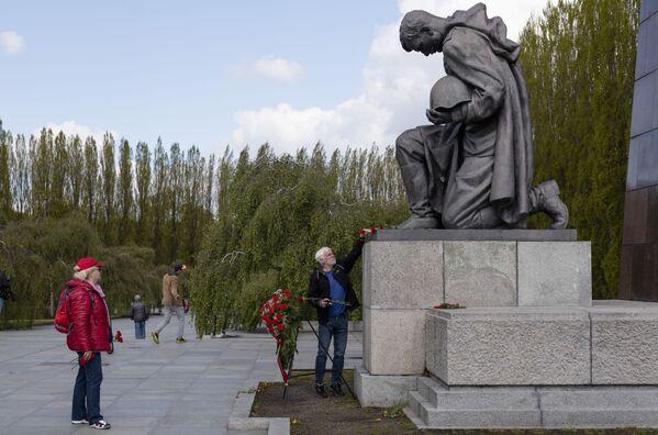 Un uomo depone fiori presso il monumento a un soldato sovietico presso il memoriale militare Treptower Park a Berlino in occasione del 76 ° anniversario della fine della Seconda Guerra Mondiale. - Sputnik Italia