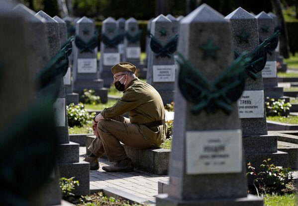 Un uomo rende omaggio alle tombe dei soldati russi nel cimitero Olshansky a Praga in occasione del 76° anniversario della fine della Seconda Guerra Mondiale. - Sputnik Italia