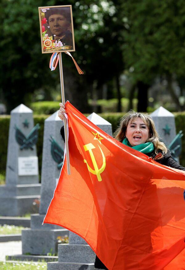 Una donna con una bandiera sovietica e il ritratto di un veterano sul territorio del cimitero Olshansky a Praga, Repubblica Ceca. - Sputnik Italia