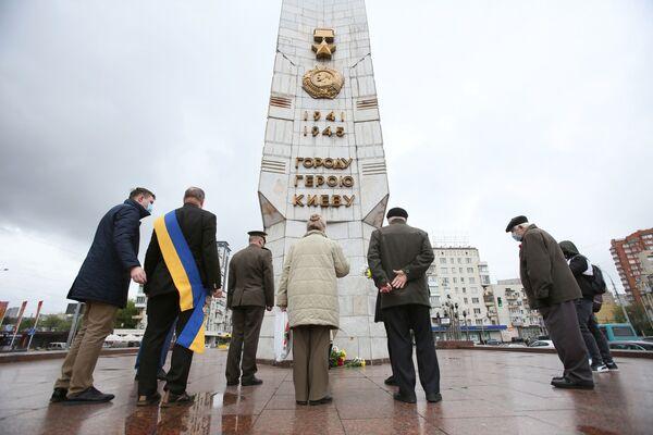 Persone depongono fiori all'obelisco della Città-Eroe Kiev in Piazza della Vittoria. - Sputnik Italia