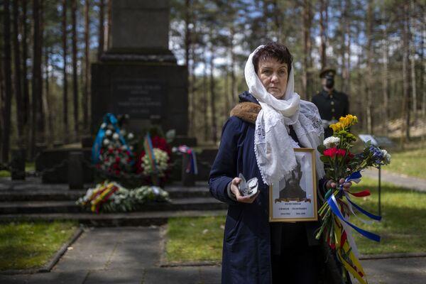 Una donna con il ritratto di un veterano al memoriale di Paneriai a Vilnius durante la cerimonia per il 76° anniversario della fine della Seconda Guerra Mondiale. - Sputnik Italia