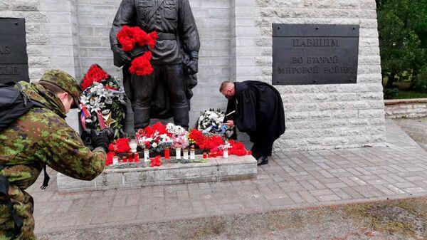 Il cappellano delle forze di difesa estoni depone una corona di fiori al monumento ai caduti nella Seconda Guerra Mondiale nel cimitero militare di Tallinn. - Sputnik Italia