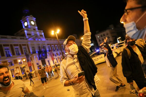 Un uomo con mascherina festeggia nella piazza Puerta del Sol, a Madrid - Sputnik Italia