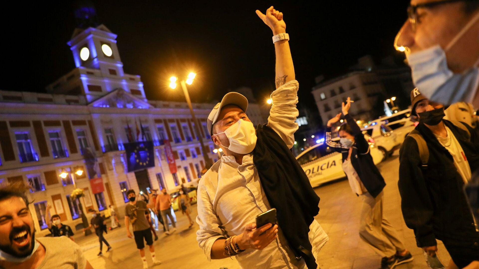 Un uomo con mascherina festeggia nella piazza Puerta del Sol, a Madrid - Sputnik Italia, 1920, 08.06.2021