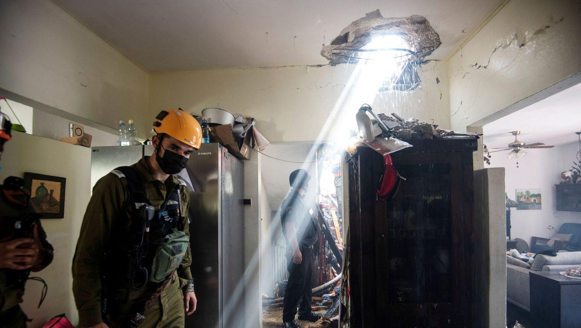 Солдаты работают у здания, поврежденного ракетой, запущенной из сектора Газа, в Ашдоде, на юге Израиля - Sputnik Italia, 1920, 14.05.2021