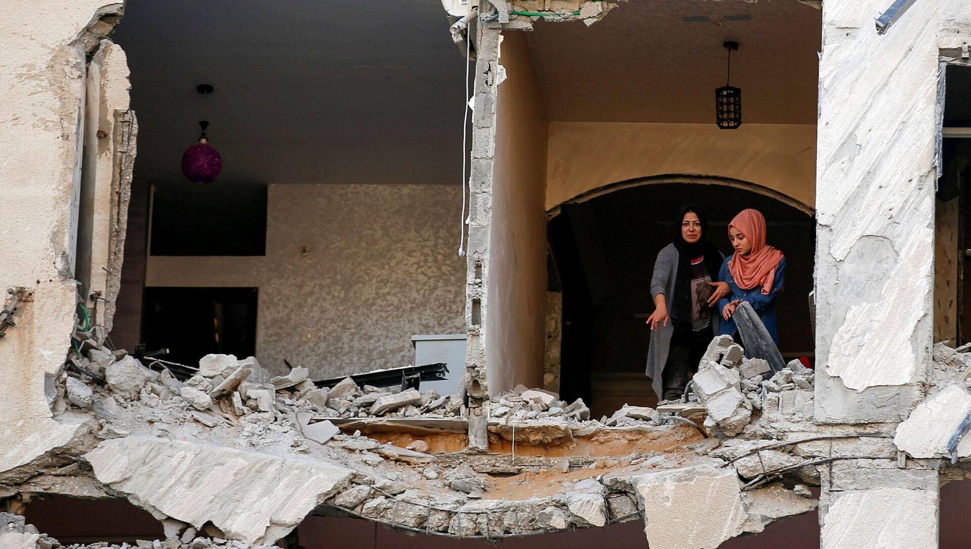 Палестинцы осматривают свой дома, который был поврежден в результате израильского авиаудара, на фоне вспышки израильско-палестинского конфликта, в городе Газа - Sputnik Italia, 1920, 12.05.2021