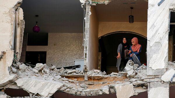 Палестинцы осматривают свой дома, который был поврежден в результате израильского авиаудара, на фоне вспышки израильско-палестинского конфликта, в городе Газа - Sputnik Italia