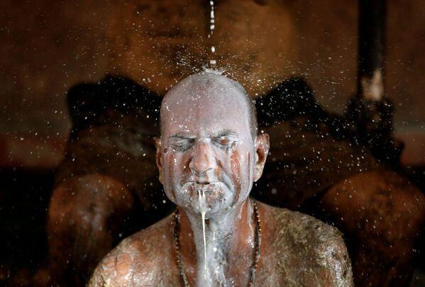 Un uomo indiano si lava con il latte dopo aver usato lo sterco di vacca  - Sputnik Italia