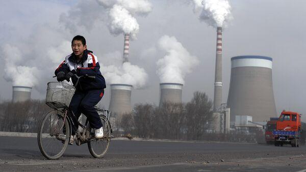 Мальчик на велосипеде напротив электростанции в Китае  - Sputnik Italia
