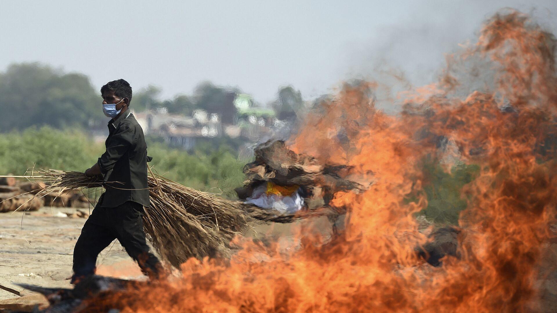 Рабочий проходит мимо горящего погребального костра человека, умершего из-за коронавируса Covid-19, Индия  - Sputnik Italia, 1920, 24.06.2021