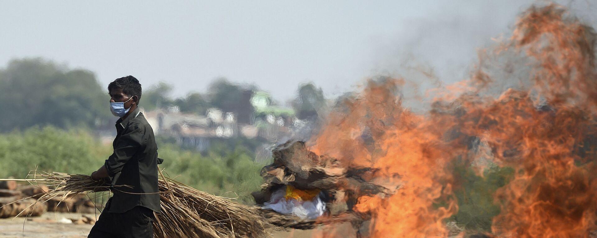 Рабочий проходит мимо горящего погребального костра человека, умершего из-за коронавируса Covid-19, Индия  - Sputnik Italia, 1920, 23.05.2021