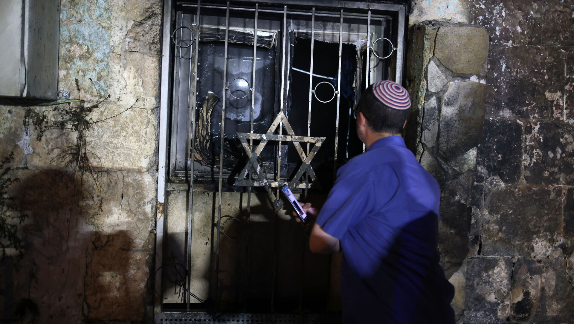 An Israeli man looks inside a synagogue, after it was set on fire by Arab-Israelis, in the mixed Jewish-Arab city of Lod on May 14, 2021, during clashes between Israeli far-right extremists and Arab-Israelis - Sputnik Italia, 1920, 14.05.2021