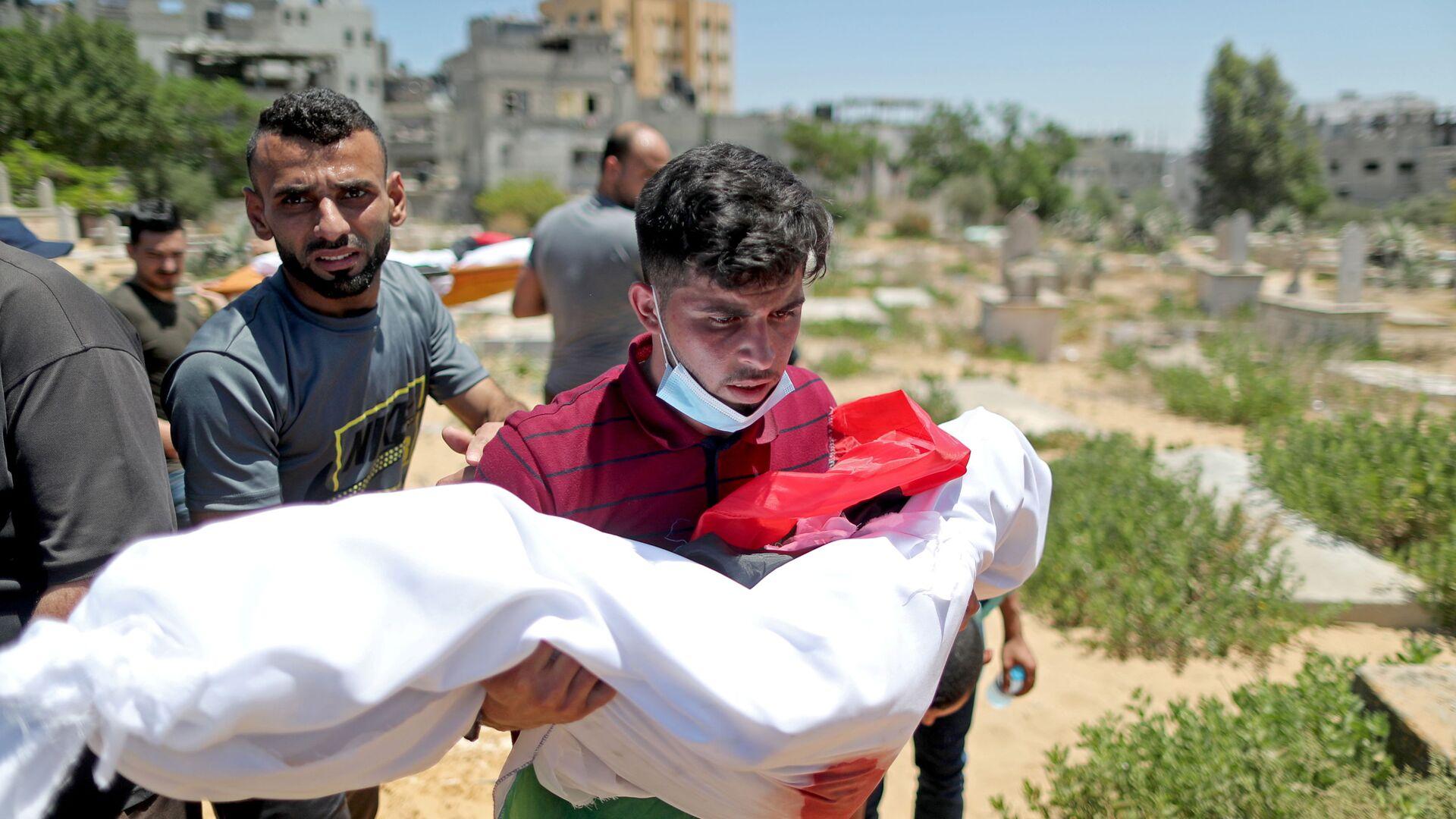 Un uomo porta il corpo di un bambino palestinese della famiglia Al-Hadidi, che è stato ucciso in un divampare di violenza israelo-palestinese - Sputnik Italia, 1920, 16.05.2021