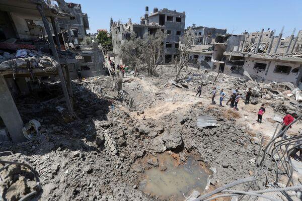 I palestinesi si radunano davanti alle loro case distrutte dopo gli attacchi aerei israeliani nella Striscia di Gaza, 14 maggio 2021 - Sputnik Italia