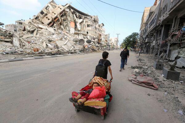 I palestinesi fuggono dalle loro case mentre gli attacchi aerei israeliani colpiscono la Striscia di Gaza, 14 maggio 2021 - Sputnik Italia