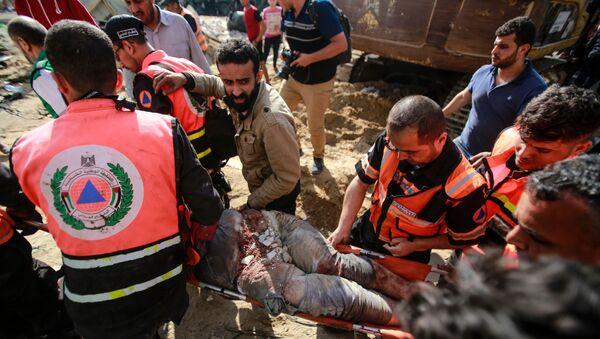 I soccorritori tirano fuori le persone dalle macerie dopo un attacco aereo israeliano - Sputnik Italia