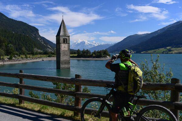 Un ciclista scatta una foto della chiesa della città vecchia di Curon, sommersa nel lago di Resia nel comune di Curon Venosta, a circa 100 km a nord-ovest di Bolzano, nel nord Italia. - Sputnik Italia