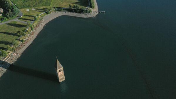 Per decenni, l'unico segno del villaggio perduto di Curon è stato il curioso aspetto della guglia di una chiesa del XIV secolo che si ergeva al centro di un lago. - Sputnik Italia