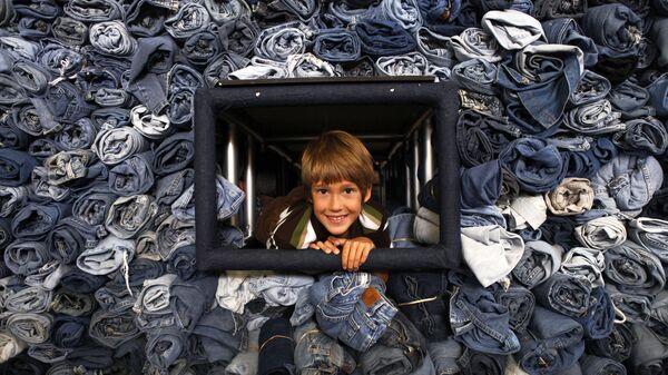 Эрек Хэнсон, 9 лет, из Кертиса, штат Огайо, высовывает голову из витрины с 33 088 парами джинсов, которые были собраны журналом National Geographic Kids для переработки в теплоизоляционный материал для жилья в Вашингтоне, 2009 год - Sputnik Italia