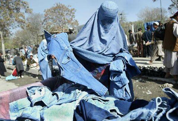 Una donna afghana sceglie blue jeans e giacche nelle strade di Kabul, in Afghanistan, 20 aprile 2003. Con poche o quasi nessuna nuova opportunità di lavoro in Afghanistan, le persone cercano di fare soldi vendendo merci per le strade. Questa nazione dell'Asia centrale è tra le più povere del mondo. - Sputnik Italia
