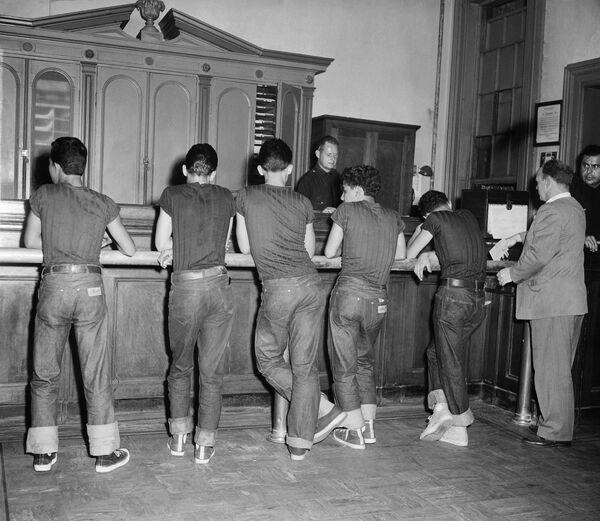 5 ragazzi, tutti in blue jeans e la maglietta scura, stanno di fronte al poliziotto alla stazione di polizia a New York, 31 luglio 1954. - Sputnik Italia