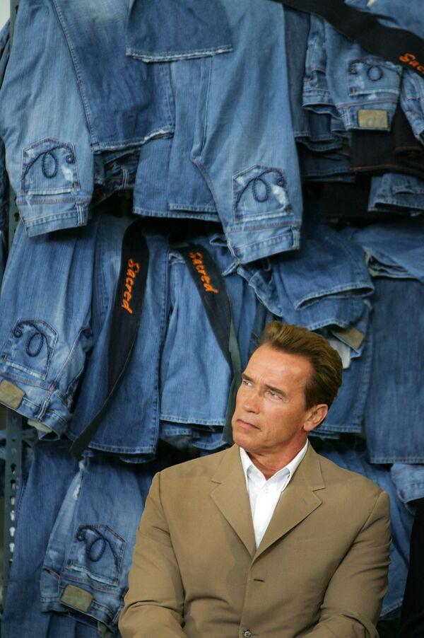 Arnold Schwarzenegger siede vicino ai jeans in denim presso lo stabilimento di produzione di indumenti Blue Cop, 2015. - Sputnik Italia