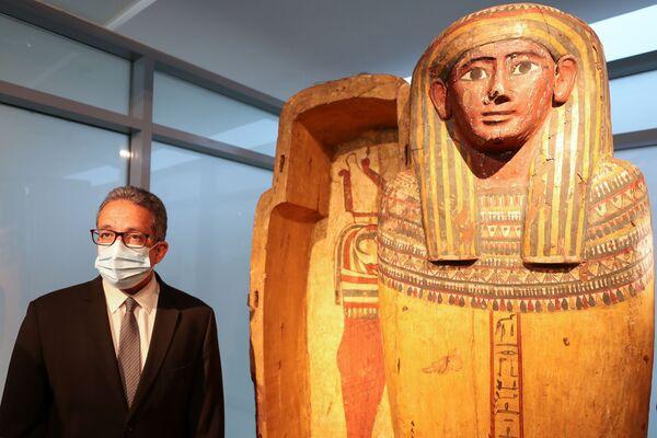 Il ministro egiziano del Turismo e delle Antichità Khaled El-Enany posa accanto a un sarcofago nel nuovo museo dell'aeroporto internazionale del Cairo, al Cairo, in Egitto, il 18 maggio 2021. - Sputnik Italia