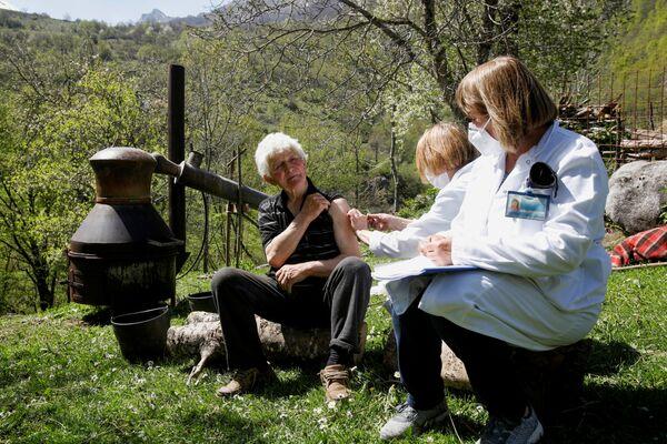 Un uomo riceve un vaccino contro il COVID-19 vicino a un pentola di brandy nel villaggio di montagna in Montenegro. - Sputnik Italia