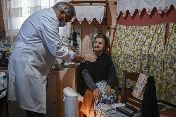 Il dottore visita una signora anziana per vaccinarla, in Grecia. - Sputnik Italia